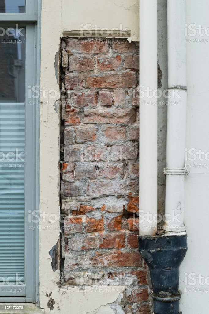 Brick House wall with flaking plaster stock photo