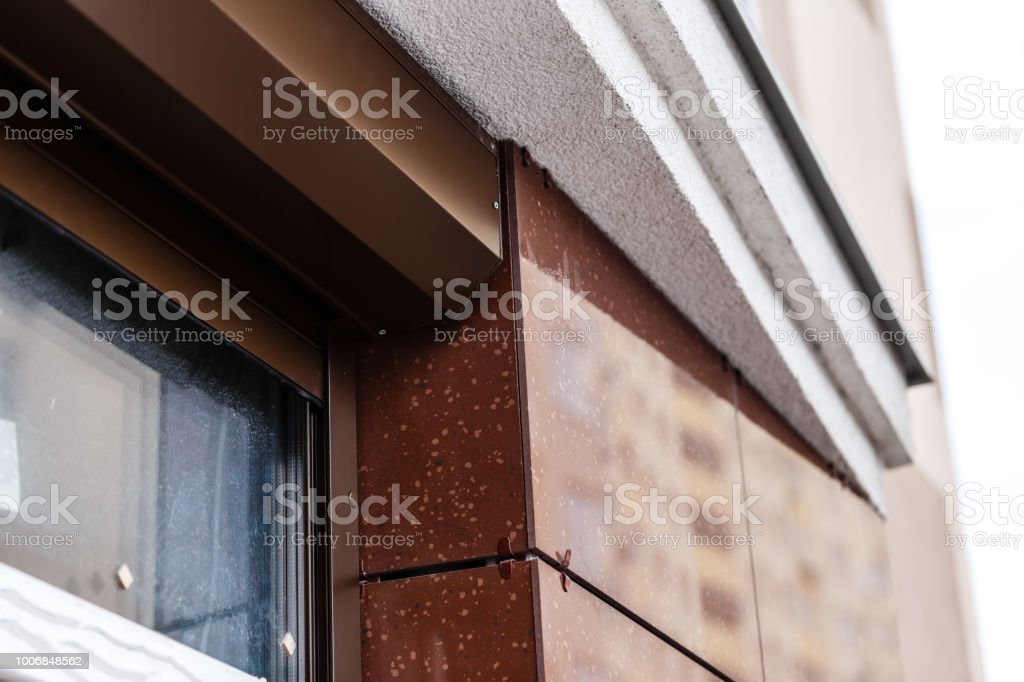 Brick house windows with rolling shutter for house protection stock photo