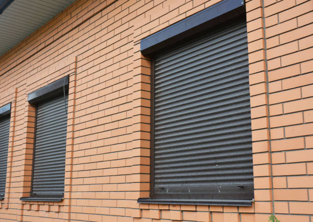 Brick House Windows with rolling shutter for house protection. stock photo