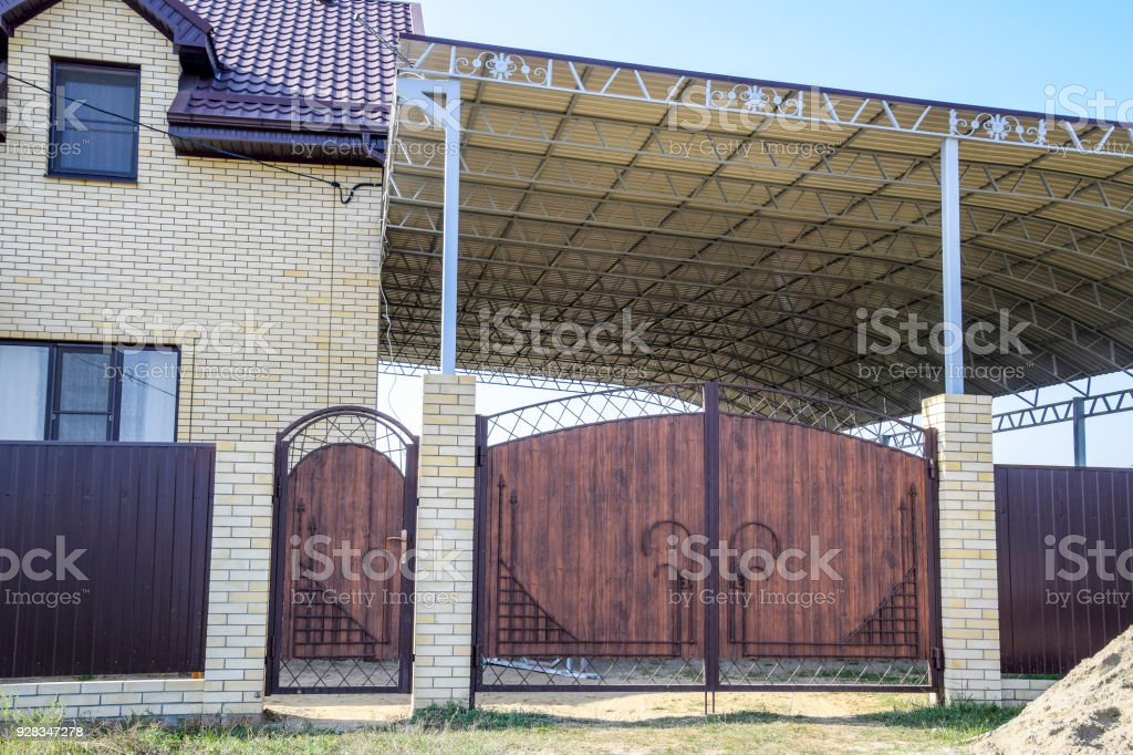Fotografía de Casa De Ladrillo Con Una Cerca Y Puertas Un Toldo ...