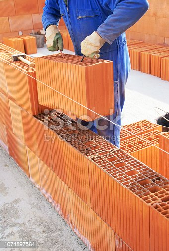 istock Brick laying for house construction 1074897564