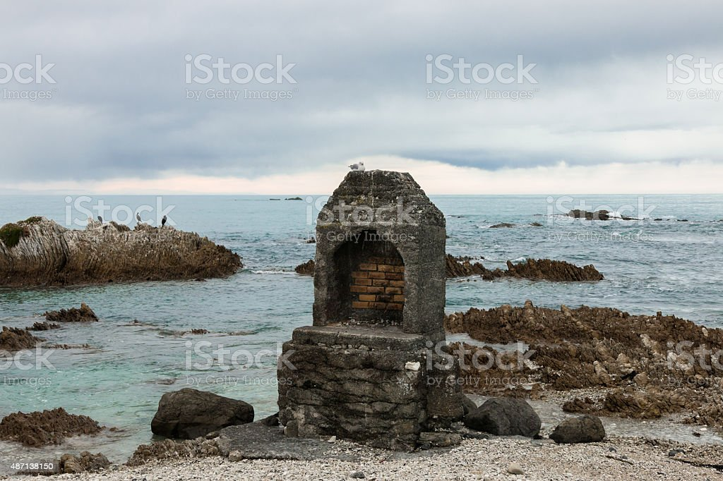Brick old-fashioned fireplace on ocean shore stock photo