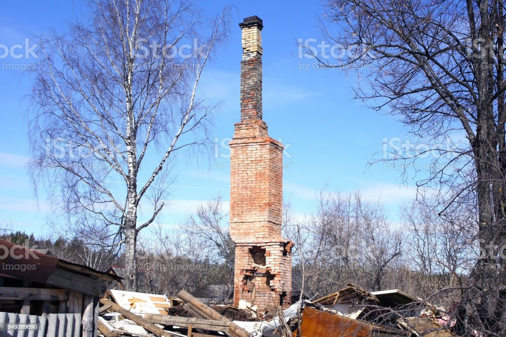 Brick oven with a pipe from the burnt house. Ruins after the fire of a wooden house. High pipe from the furnace against the blue sky. spring, Russia. stock photo