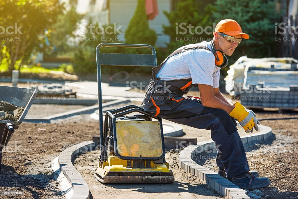 Brick Paver Worker Brick Paver Worker Resting on His Soil Plate Compactor While at Work. Adult Stock Photo