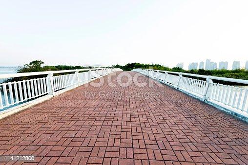 Brick pedestrian bridge over the sea.
