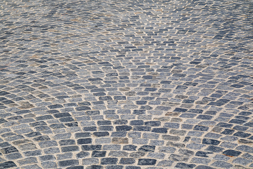 istock Brick stone street pavement close up background. Empty dark stone pavement on old town ancient street, abstract cobblestone paved road pattern 1225897903