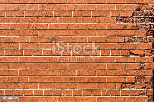 A background of classic red bricks with a crumbling edge on the right side.