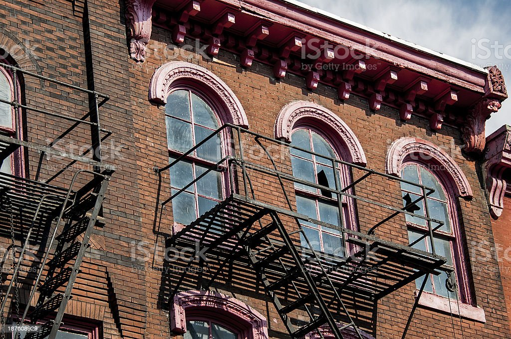 Brick Urban Apartment Buildings with Broken Windows and Fire Escapes stock photo