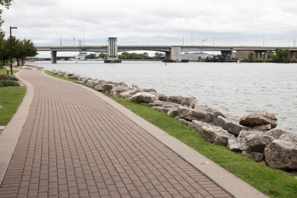 brick walkway along the fox river in green bay, wisconsin - green bay wisconsin stock photos and pictures