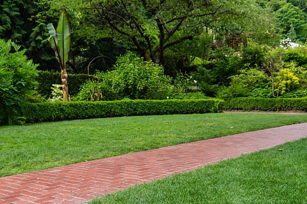Brick walkway leading through a garden stock photo