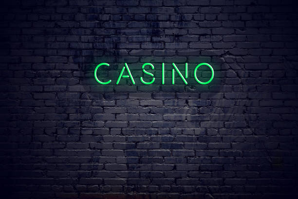 Brick wall at night with neon sign casino