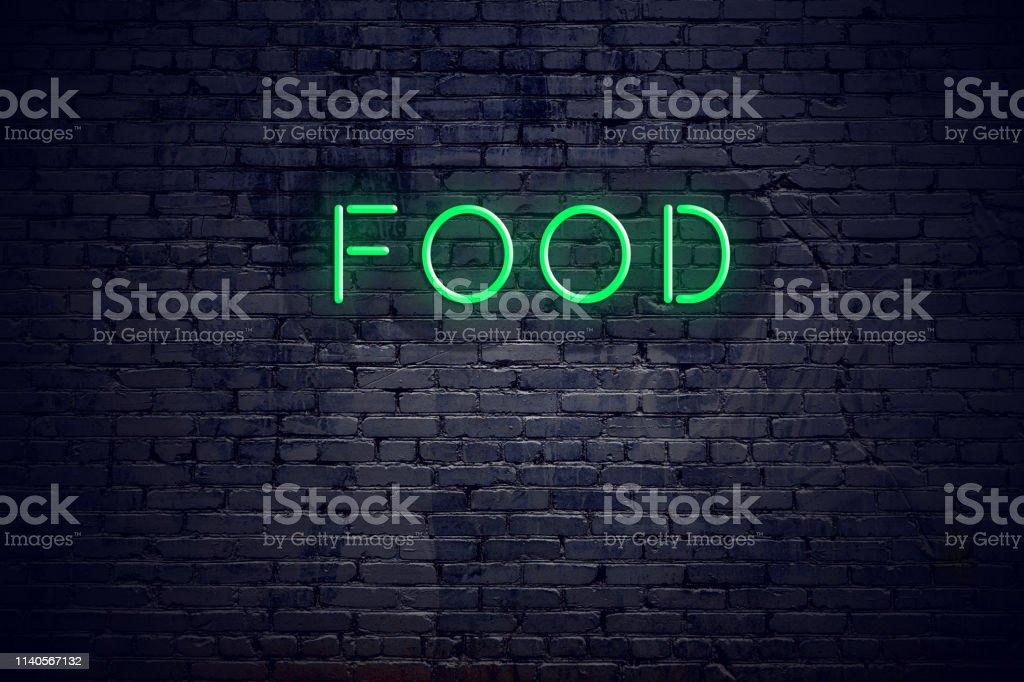 Brick wall at night with neon sign food Brick wall at night with neon sign food. Advice Stock Photo