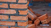 brick wall background on front and pile of bricks prepared for brickwork or masonry building brickwork in construction building