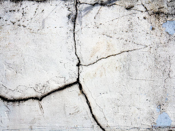 Brick wall covered with cracked plaster stock photo