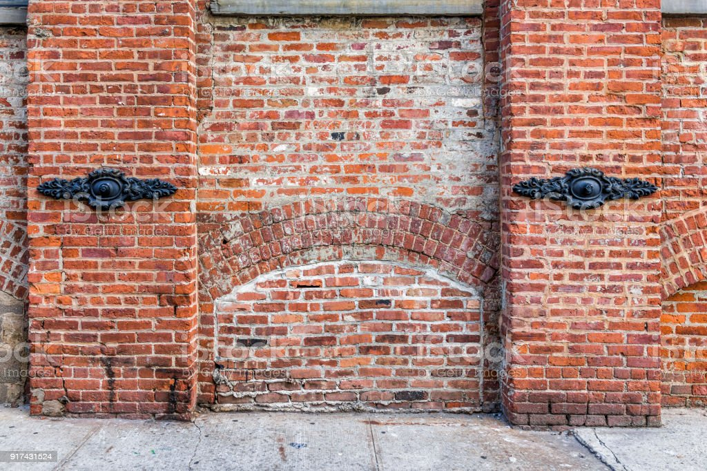 Brick wall in Brooklyn, NYC, New York City front view exterior, grunge old architecture dirty by sidewalk stock photo