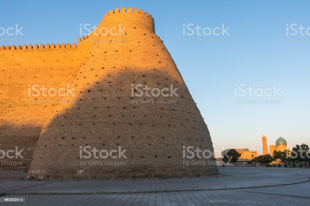 Brick wall of Ark fortress and Kalon Mosque on the backgorund, Bukhara, Uzbekistan stock photo