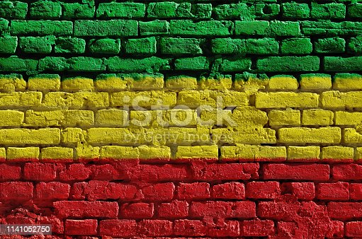 136699912 istock photo Brick wall painted in green, yellow and red. Rastaman flag 1141052750