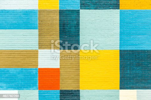 old historic brick wall painted in rainbow colors