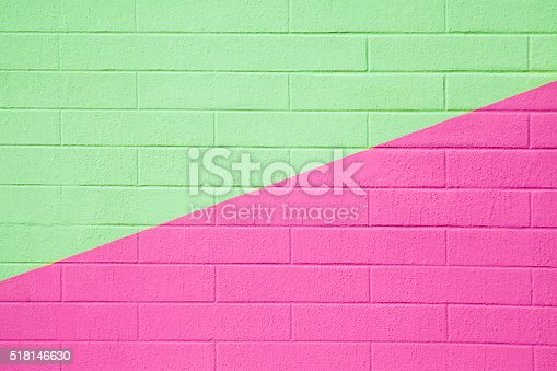 Brick wall painted pink and green, divided in two by a diagonal line, background full frame image, copy space available.
