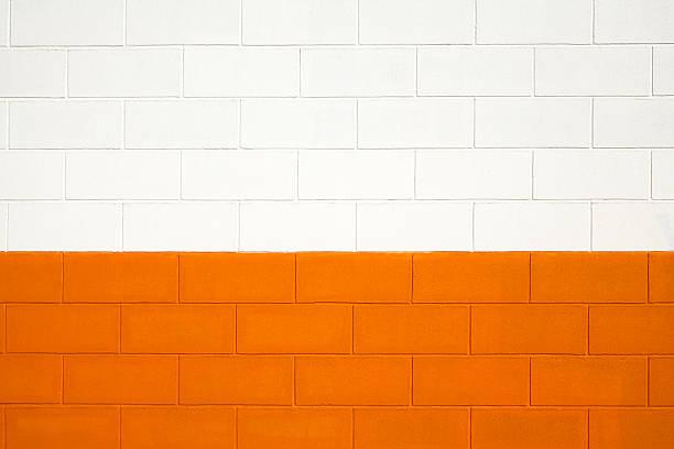 brick wall painted white and orange, background full frame. - betonblock wände stock-fotos und bilder
