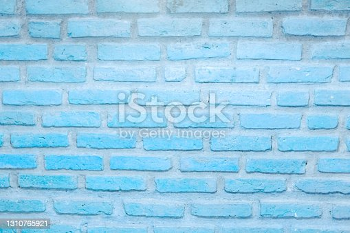 Brick wall painted with pale blue paint pastel calm tone texture background. Brickwork blue and stonework flooring interior rock old pattern clean concrete uneven bricks design for background.