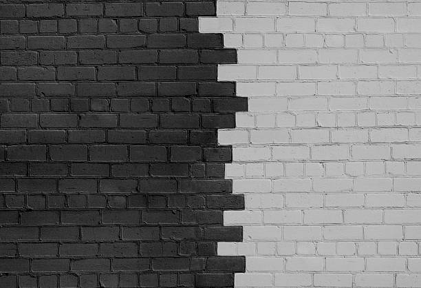 brick wall parted on dark and light sides - separation stock photos and pictures