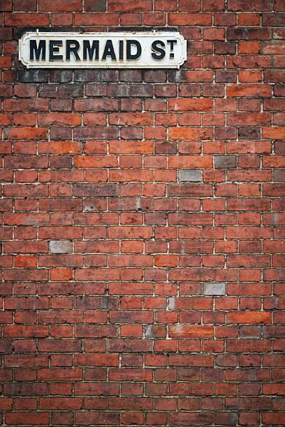 brick wall-street-schild meerjungfrau st rye uk - straßenschild stock-fotos und bilder