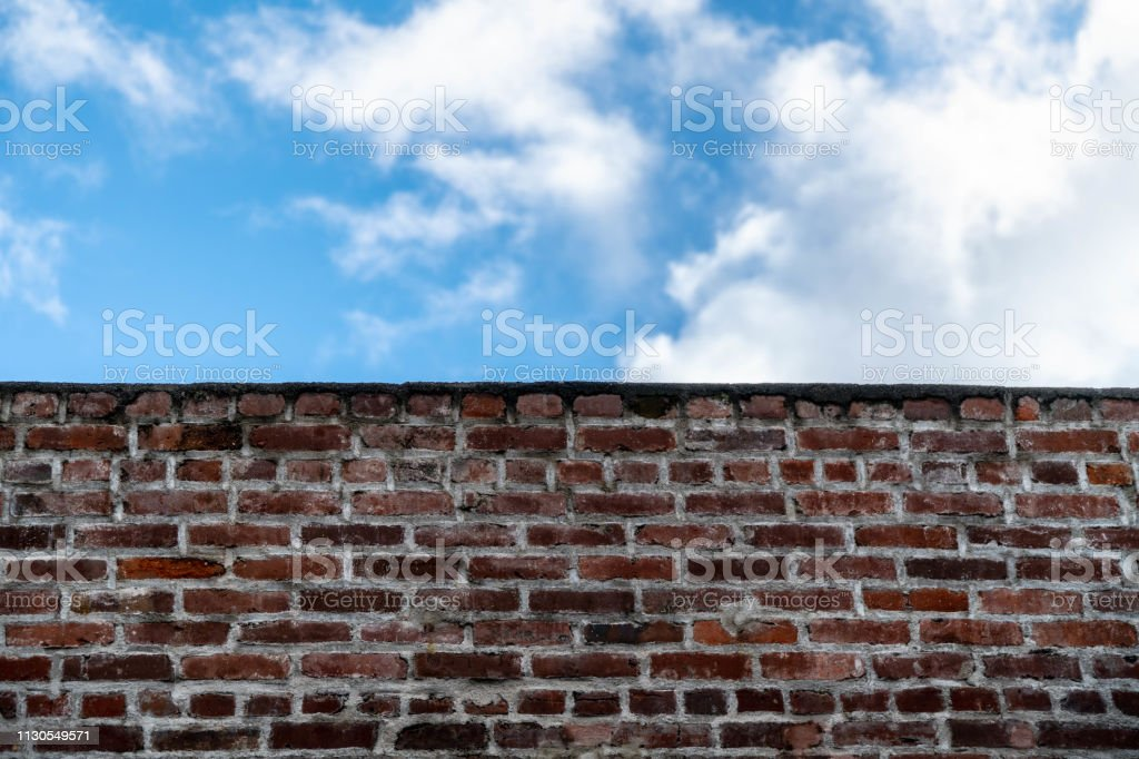 Weathered brick wall with an empty sign.