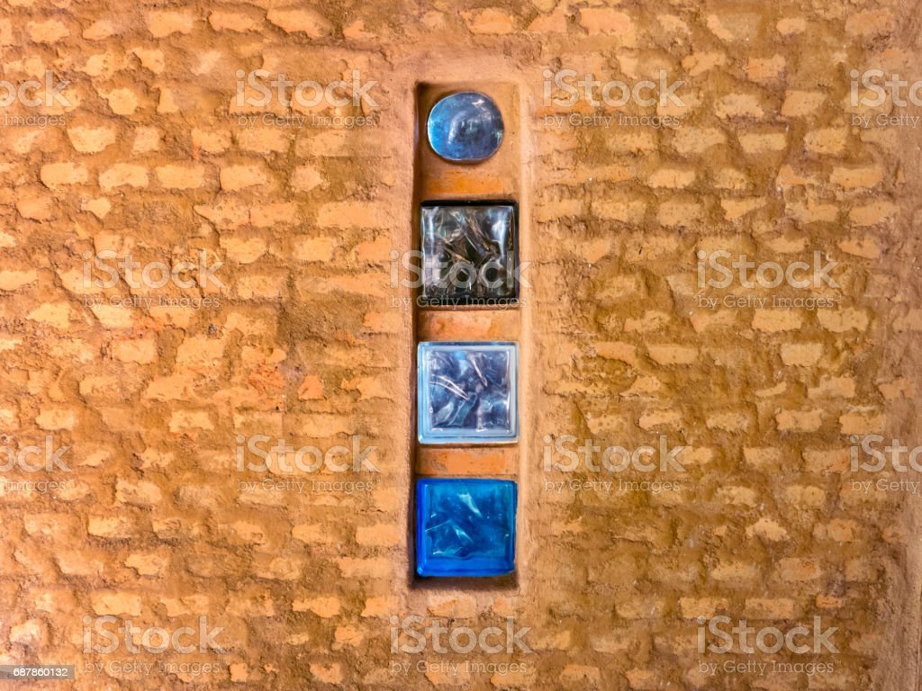 Brick wall with colored glass brick as windows in a rustic house stock photo