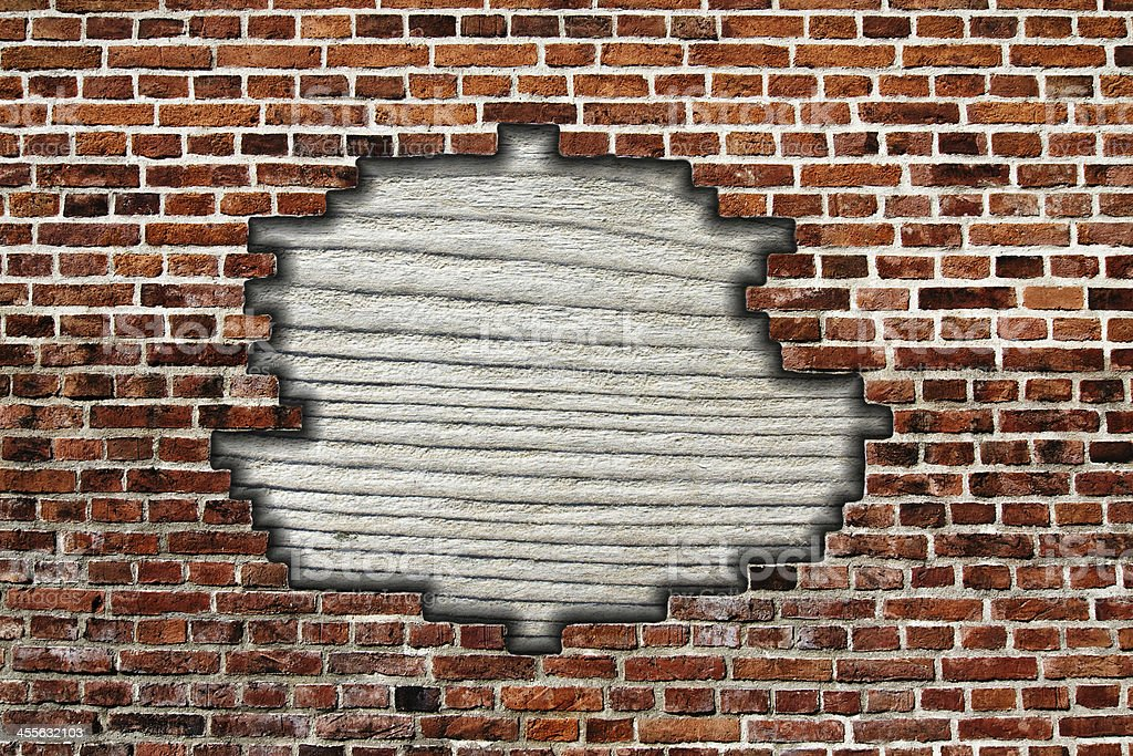 brick wall with hole and wooden board stock photo