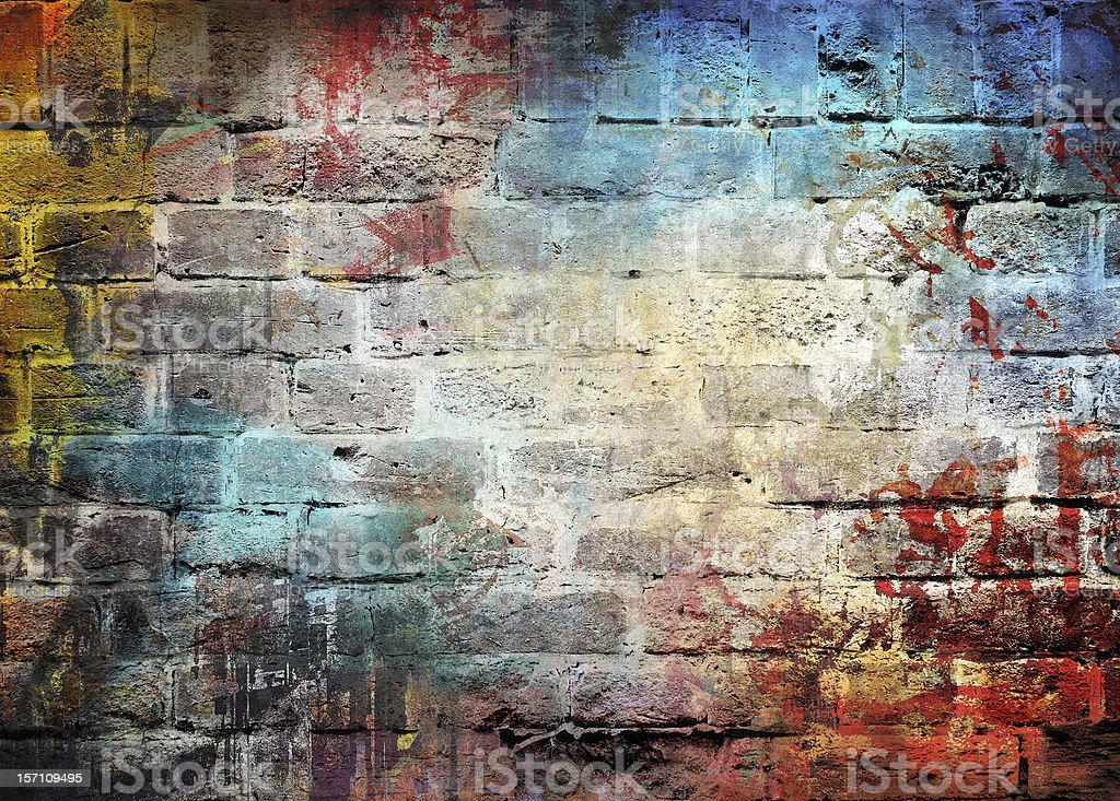 Brick wall with letters and different colors splattered on royalty-free stock photo