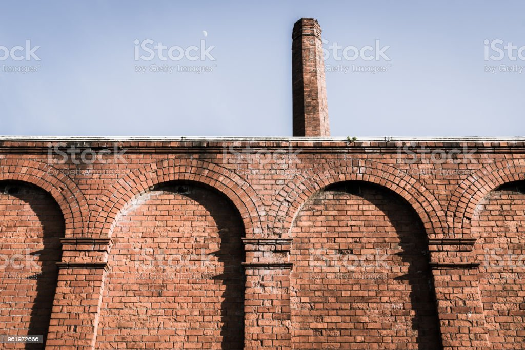 Brick wall with supporting arches and chimney stock photo