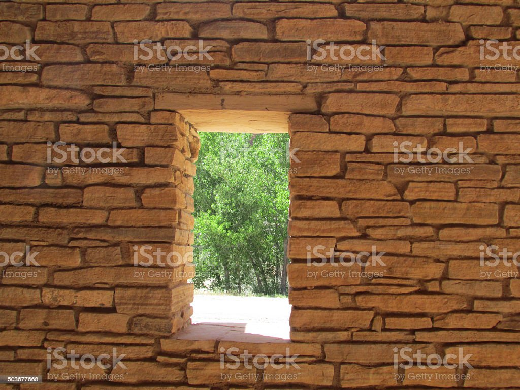 Old brick wall with window looking out at a forest in Utah.