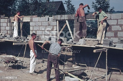 Near Augsburg, Bavaria, 1961. Craftsmen (masons) build a house wall on a property.