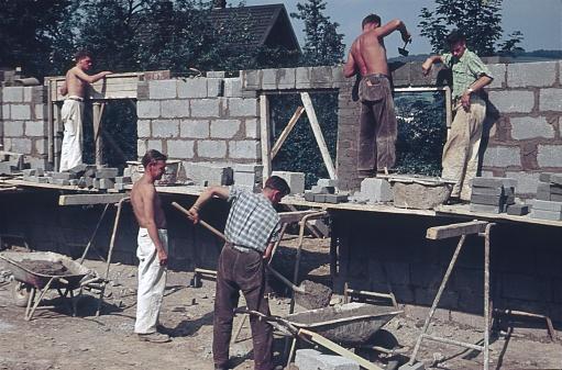 Near Augsburg, Bavaria, 1961. Craftsmen (masons) build a house wall on a property.