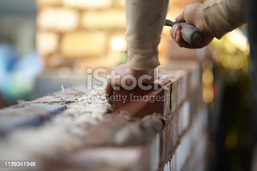 A bricklayer works on a new domestic kitchen extension using reclaimed bricks. Images show general construction and a cross section of the wall revealing insulation and outer and inner skins