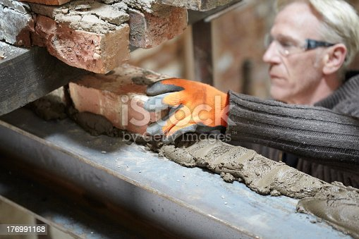Bricklayer building an internal wall on steelwork