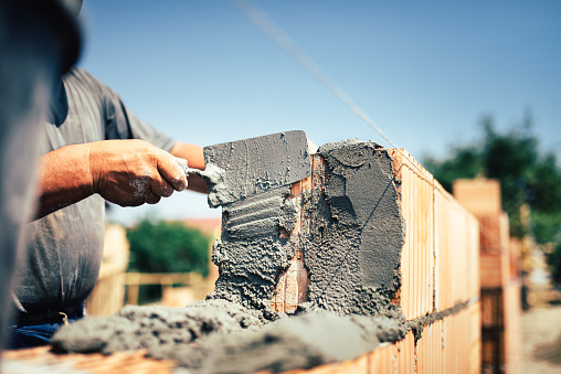 Bricklayer construction worker installing brick masonry on exterior wall with trowel putty knife