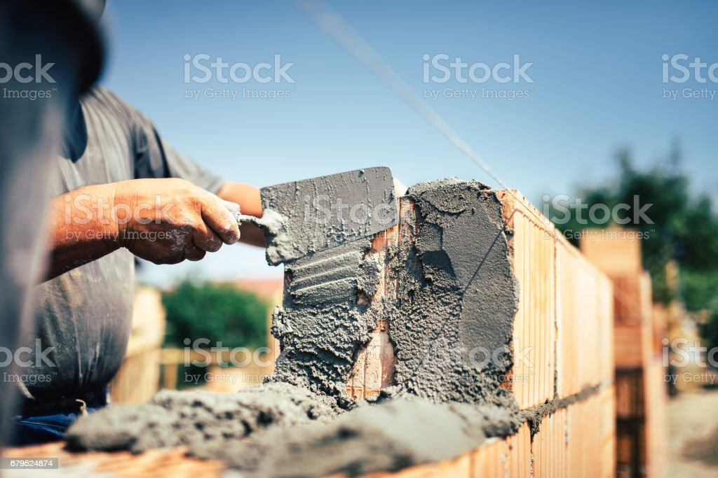 Bricklayer construction worker installing brick masonry on exterior wall with trowel putty knife – Foto