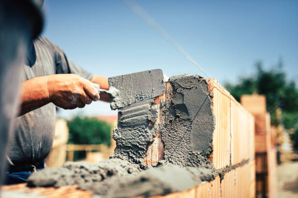 Bricklayer construction worker installing brick masonry on exterior wall with trowel putty knife stock photo