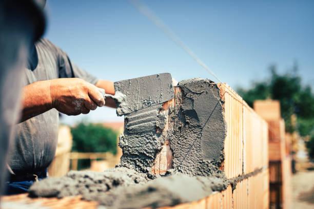 Maurer-Bauarbeiter Ziegelmauerwerk mit Kelle Kitt Messer auf Außenwand zu installieren – Foto