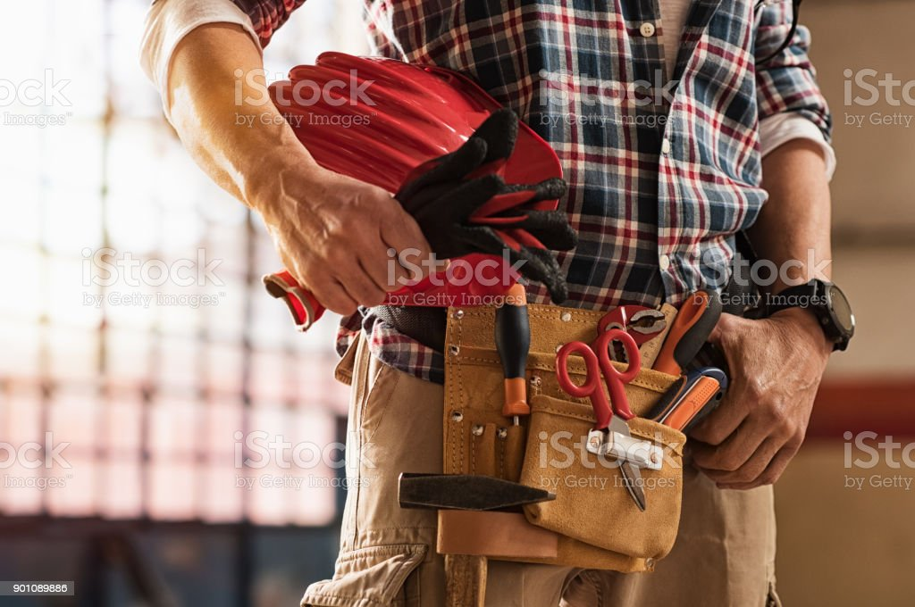 Bricklayer holding construction tools stock photo
