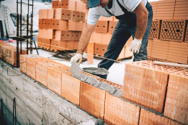 Bricklayer industrial worker installing brick masonry on exterior wall with trowel putty knife stock photo