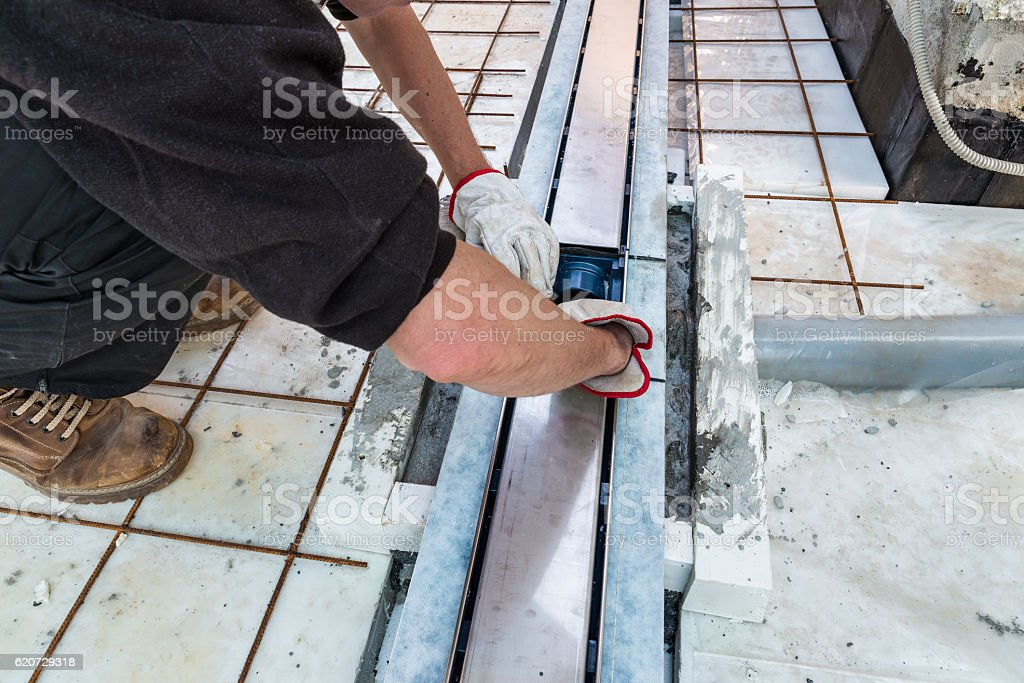 Bricklayer is installing a drain gully for drainage of terrace stock photo