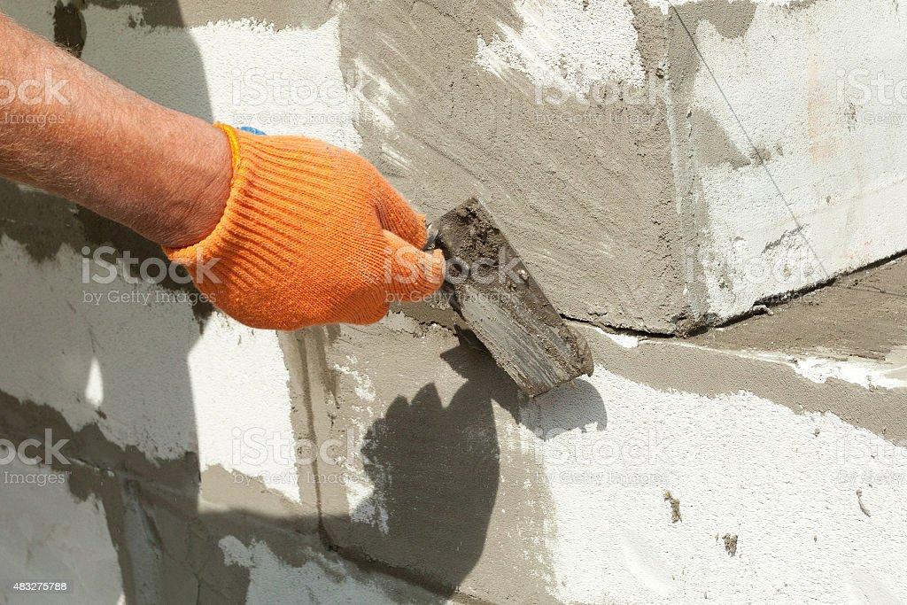 Bricklayer man worker in orange gloves installing block with trowel stock photo