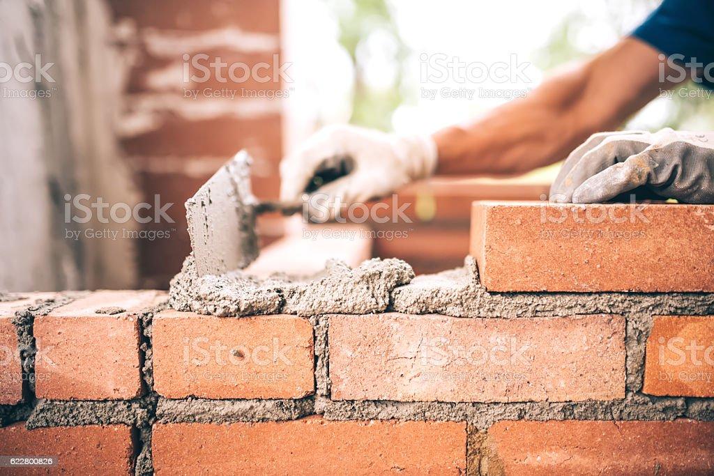 Bricklayer worker installing brick masonry on exterior wall royalty-free stock photo