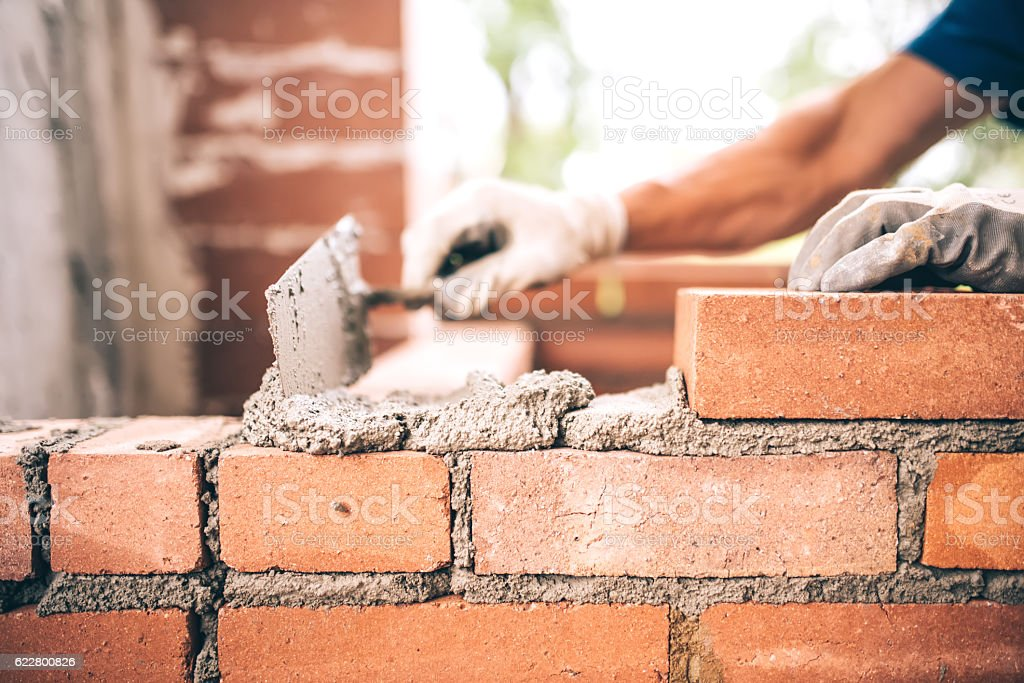 Bricklayer worker installing brick masonry on exterior wall stock photo