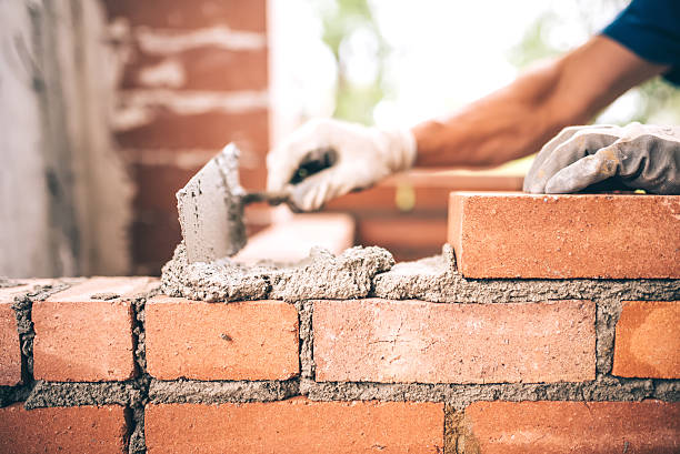 bricklayer worker installing brick masonry on exterior wall - construction material stock photos and pictures