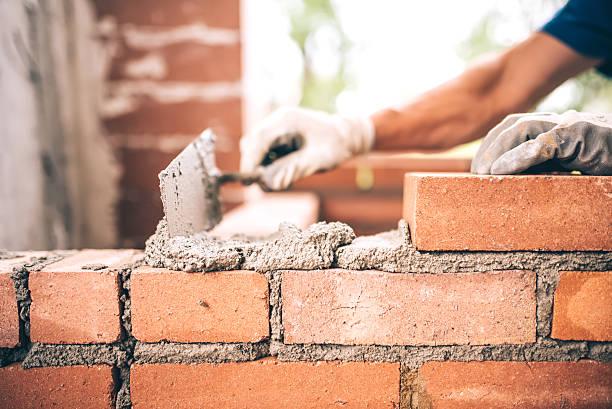 bricklayer worker installing brick masonry on exterior wall - matériau de construction photos et images de collection