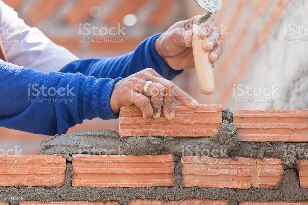 Bricklayer working in construction site stock photo